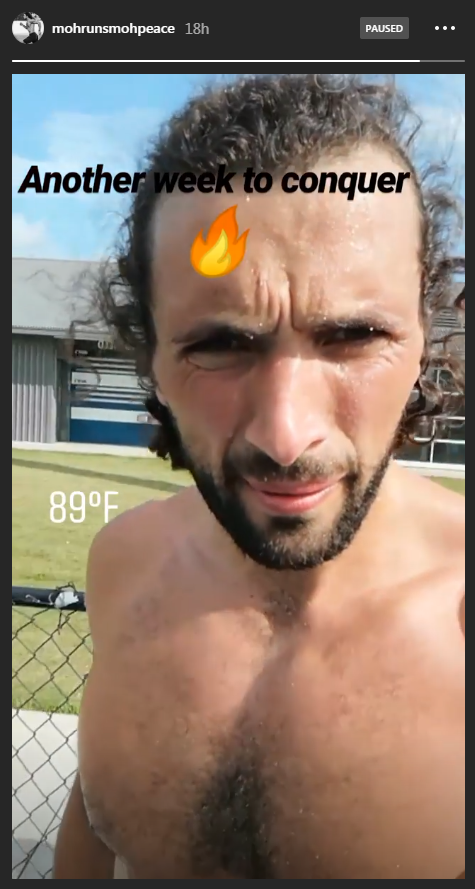 """Screenshot of Mohammed's Instagram story, looking directly at the camera as beads of sweat roll down his forehead. He captions his story with """"Another week to conquer"""" and a fire blaze emoji, and the current temperature of 89 degrees F."""